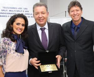 Alexandre, com a placa recebida, ladeado por Vanessa Morales e Luciano